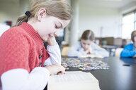 Schoolgirl reading book on table in school break room - WESTF24144