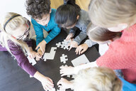 Pupils playing jigsaw puzzle in school together - WESTF24150