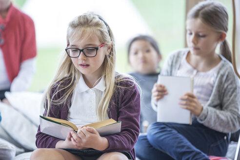 Schoolgirls reading books in school break room - WESTF24153