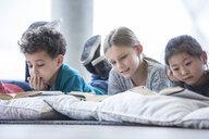 Pupils lying on the floor reading books in school break room - WESTF24156