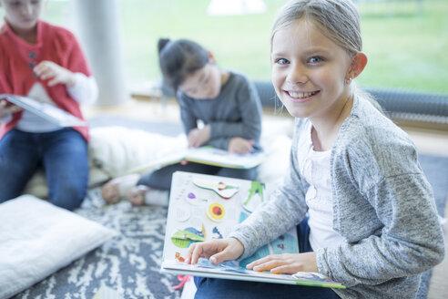 Portrait of smiling schoolgirl sitting on the floor with book in school break room - WESTF24165