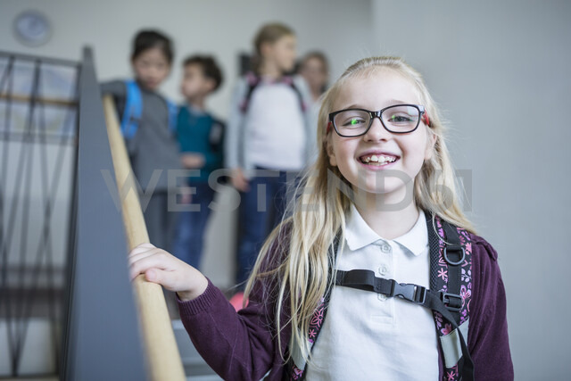 Portrait of happy schoolgirl with classmates on staircase leaving school - WESTF24168