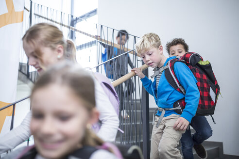 Happy pupils on staircase leaving school - WESTF24171