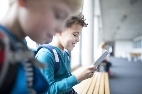 Smiling pupils with tablet on school corridor - WESTF24174