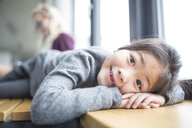 Portrait of smiling schoolgirl lying on bench in school - WESTF24177