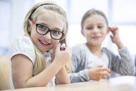 Portrait of smiling schoolgirl in class holding mouse - WESTF24201