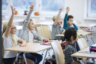 Happy pupils raising their hands in class - WESTF24204