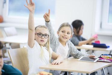 Schoolgirls with tablet raising their hands in class - WESTF24207