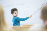 Schoolboy explaining formula at whiteboard in class - WESTF24210