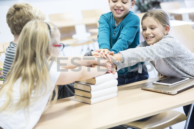 Happy pupils stacking hands on books in class - WESTF24213