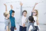 Happy pupils raising their hands at whiteboard with formulas in class - WESTF24216