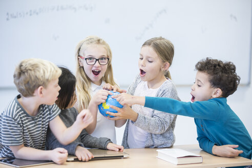 Happy pupils holding globe together in class - WESTF24219