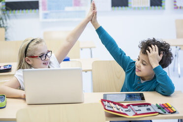 Schoolboy and schoolgirl with laptop high fiving in class - WESTF24225