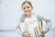 Portrait of happy schoolgirl carrying books in class - WESTF24231