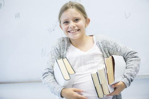Portrait of happy schoolgirl carrying books in class - WESTF24231
