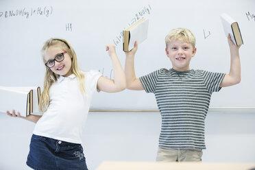 Portrait of happy schoolgirl and schoolboy carrying books in class - WESTF24234