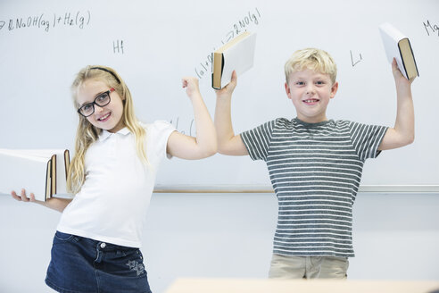 Portrait of happy schoolgirl and schoolboy carrying books in class - WESTF24234