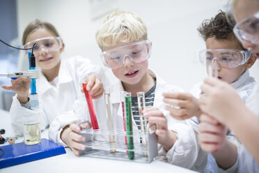 Pupils in science class experimenting with liquids in test tubes - WESTF24240
