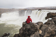 Iceland, man sitting at Godafoss waterfall - KKAF01036