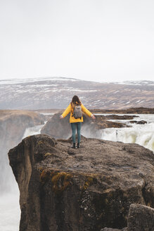 Iceland, woman standing at Godafoss waterfall - KKAF01039