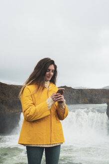 Iceland, woman with cell phone at Godafoss waterfall - KKAF01042