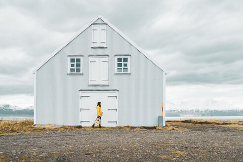 Iceland, woman with guitar walking at lonely house - KKAF01051