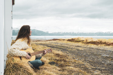 Iceland, woman sitting in rural landscape playing guitar - KKAF01054