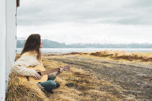 Iceland, woman sitting in rural landscape playing guitar - KKAF01054