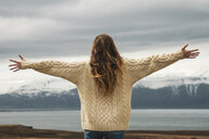 Iceland, woman standing at lakeside with outstretched arms - KKAF01060