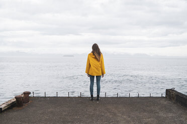 Iceland, woman standing at the sea - KKAF01063