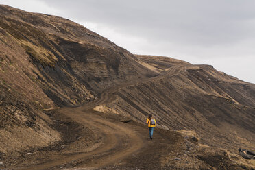 Iceland, woman walking in deserted landscape - KKAF01066