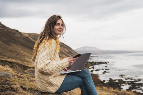 Iceland, woman using laptop and cell phone at the coast - KKAF01069