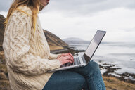 Iceland, woman using laptop at the coast - KKAF01072