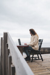 Iceland, woman using laptop at the sea - KKAF01075