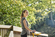 Smiling sportive young woman with bicycle in a forest - MMIF00076