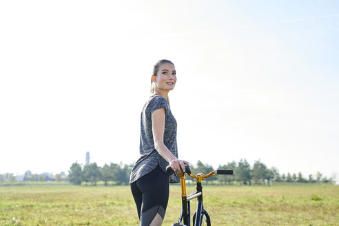 Smiling sportive young woman with bicycle on a meadow - MMIF00085