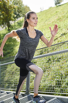 Young woman running on stairs in a park - MMIF00091