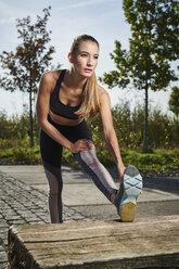 Sportive young woman stretching her leg - MMIF00094