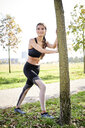 Smiling sportive young woman stretching at a tree - MMIF00097