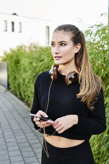Sportive young woman with headphones and cell phone outdoors - MMIF00103