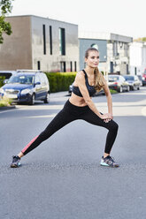 Sportive young woman stretching on a street in the city - MMIF00109
