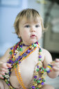 Female toddler trying on bead necklaces in kitchen - ISF05793