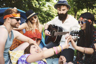 Five young adult friends playing acoustic guitar while festival camping - ISF05820