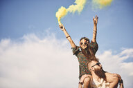 Young boho woman holding yellow smoke flare on boyfriend's shoulders at festival - ISF05835
