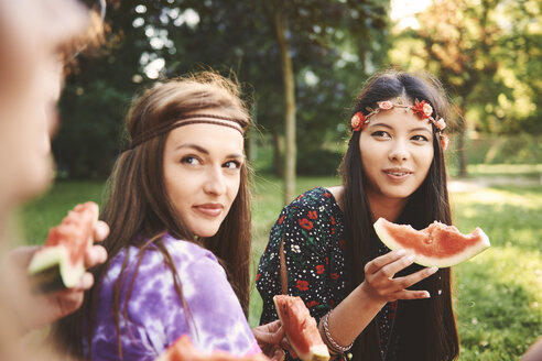 Young boho women eating melon slice at festival - ISF05838