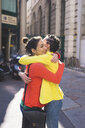 Women hugging in street, Milan, Italy - ISF05883