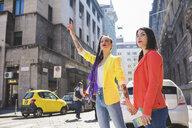 Woman on city break hailing taxi, Milan, Italy - ISF05892
