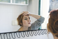 Reflection of young woman with hand on forehead looking at bathroom mirror - ISF05928