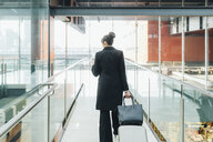Businesswoman using mobile and pulling trolley luggage, Milan, Italy - ISF05961
