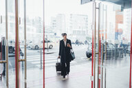 Businesswoman pulling trolley luggage into building, Milan, Italy - ISF05964